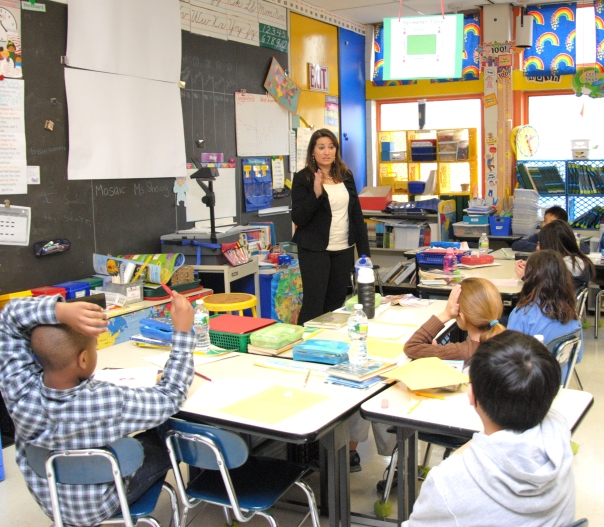 Emily Hodge, Choate, Hall & Stewart, teaches students about the importance of due process and access to justice at the Josiah Quincy Elementary School. In May 2012, 28 volunteers taught 580 students at 5 different schools about the field of law.