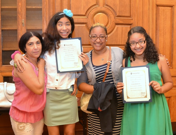 Summer Jobs students Yewellyn Sanchez and Patricia Rodriguez, who interned at the Boston Bar Association this summer, showed off their certificates while posing with family members at a reception following the graduation ceremony.