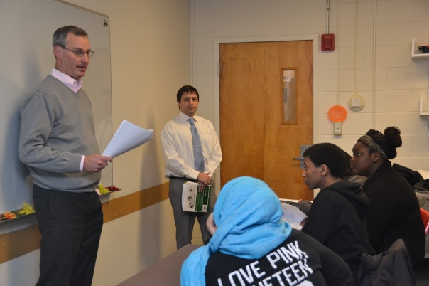 Volunteer Attorneys Steve Cohen and Eric Teasdale from Choate Hall & Stewart LLP discuss the hidden costs of buying a car with students at Edward M. Kennedy Academy for Health Careers.