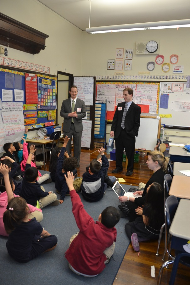 Attorneys  John McBrine and Rory Pheiffer both of Nutter McClennen & Fish LLP, holding a vote in Ms. Mulherin's 1st grade class at Sam Adam's Elementary School in East Boston.